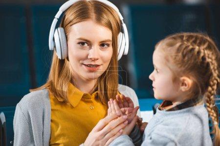 Photo pour Foyer sélectif de la musique attrayante mère écoute dans les écouteurs près de la fille - image libre de droit