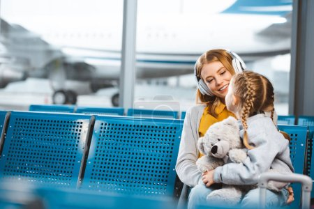 beautiful mother in headphones looking at daughter with teddy bear in departure lounge
