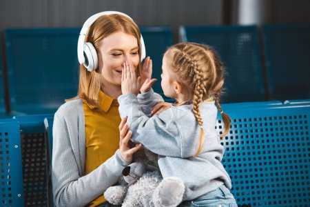 daughter touching face of beautiful mother in headphones in airport