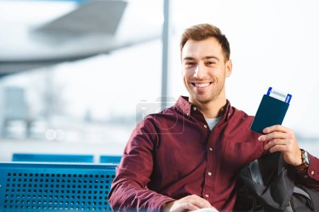 Photo pour Homme gai, détenteurs d'un passeport avec billet d'avion dans la salle d'attente de l'aéroport - image libre de droit