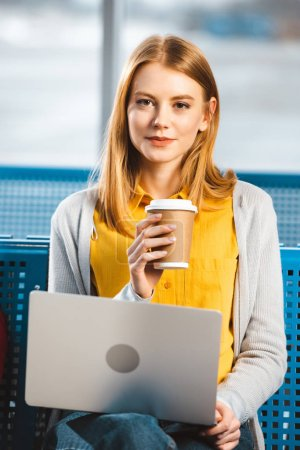 attractive woman sitting with laptop and holding paper cup in departure lounge of airport