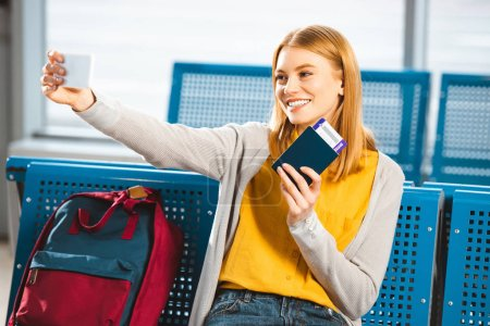 smiling woman taking selfie with passport and air ticket in waiting hall