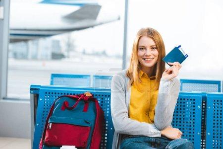 Lächelnde Frau mit Pass und Flugticket im Flughafen in der Nähe von Rucksack