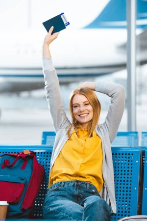 smiling woman holding passport above head in airport near backpack