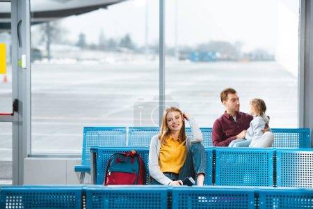 Photo pour Foyer sélectif de la femme souriante assise à l'aéroport près du sac à dos avec des gens sur le fond - image libre de droit