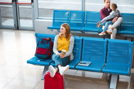 selective focus of smiling woman holding paper cup in airport near backpack with people on background
