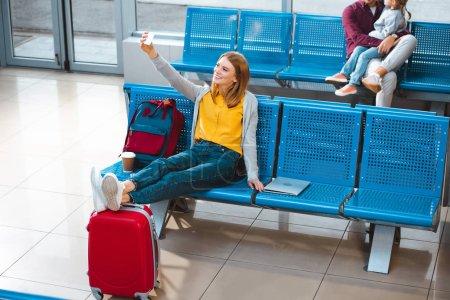 Photo pour Mise au point sélective du sourire selfie prendre femme à l'aéroport avec des gens sur fond - image libre de droit