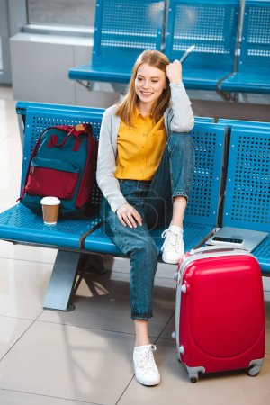 attractive woman sitting in waiting hall of airport near backpack and baggage