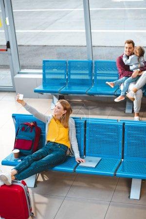 Photo pour Foyer sélectif de femme gaie prenant selfie à l'aéroport avec des gens sur fond - image libre de droit