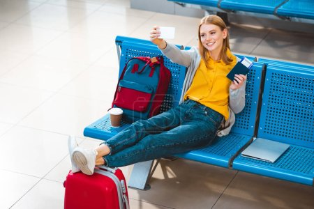 smiling woman taking selfie in airport near backpack and luggage