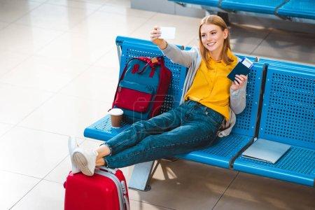 Photo pour Femme souriante tenant selfie en aéroport près de sac à dos et bagages - image libre de droit