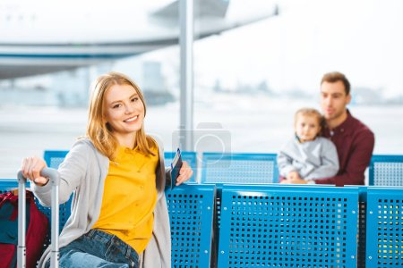 selective focus of woman holding passport with air ticket and smiling with people on background