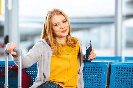 Photo pour Femme détenteurs d'un passeport avec billet d'avion et souriant à l'aéroport - image libre de droit