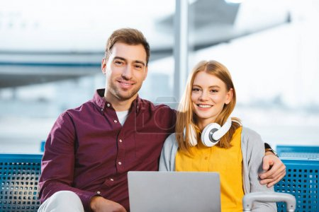 happy boyfriend and girlfriend smiling while looking at camera near laptop in airport