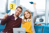cheerful boyfriend and girlfriend holding passports with air tickets in airport