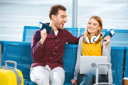 Photo for Cheerful couple holding passports with air tickets in airport near luggage - Royalty Free Image