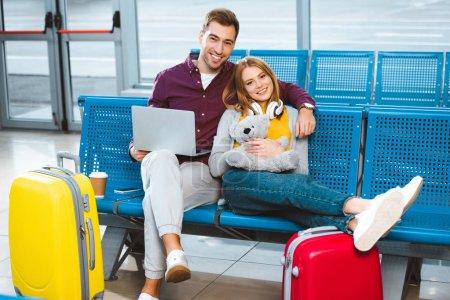 Photo pour Petit ami heureux avec ordinateur portable souriant avec petite amie tenant ours en peluche à l'aéroport - image libre de droit