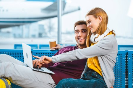 Photo pour Femme gaie tenant tasse en papier tout en pointant du doigt à l'ordinateur portable près de petit ami à l'aéroport - image libre de droit