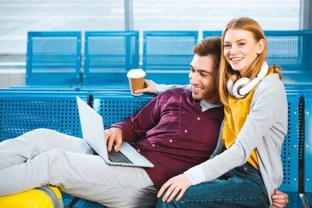 Photo pour Femme joyeuse tenant la tasse de papier près de copain avec ordinateur portable tout en étant assis dans l'aéroport - image libre de droit