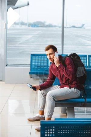 Photo pour Bel homme parler sur smartphone tout en étant assis dans la salle d'attente avec sac à dos - image libre de droit
