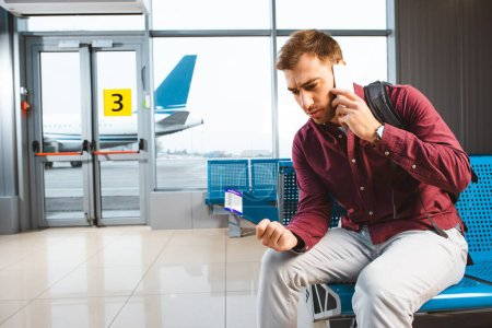 man talking on smartphone while sitting in waiting hall