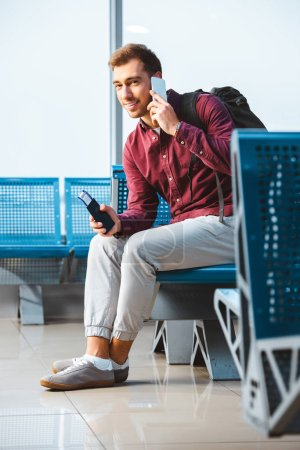 cheerful man talking on smartphone and smiling while sitting in waiting hall