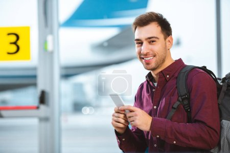 cheerful man holding smartphone and smiling in airport