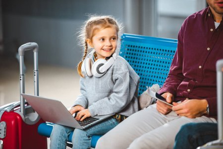 smiling kid in headphones using laptop near dad in airport