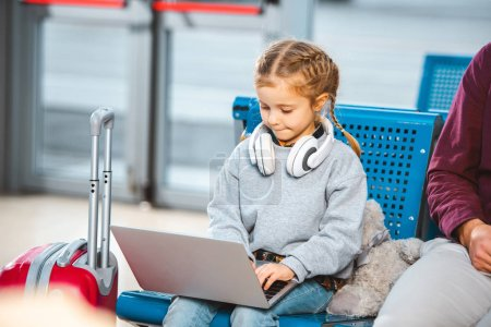 cute kid in headphones using laptop near dad in waiting hall of airport