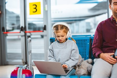 adorable child in headphones using laptop near dad in waiting hall