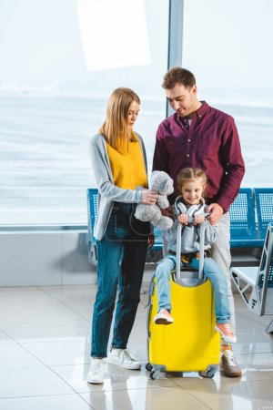 adorable child sitting on suitcase while mother holding teddy bear and standing near husband in waiting hall