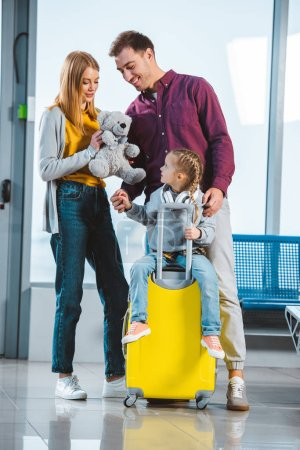 Photo for Adorable child in headphones sitting on suitcase while mother holding teddy bear and standing near husband in departure lounge - Royalty Free Image