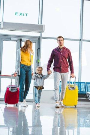 Photo pour Femme heureuse et mari, main dans la main avec une fille mignonne en salle d'embarquement - image libre de droit