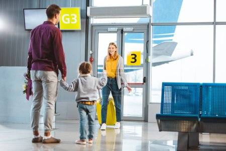 selective focus of mother with baggage looking at husband and daughter holding hands while meeting in airport