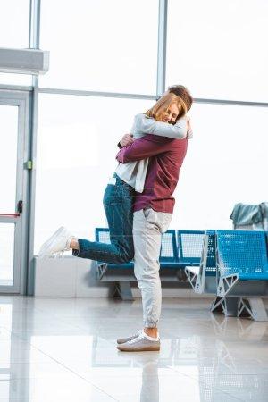 Photo pour Femme heureuse étreignant petit ami à l'aéroport - image libre de droit
