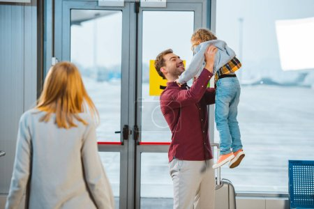 selective focus of happy father holding in arms daughter near wife in airport