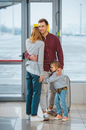 Photo pour Bel homme étreignant femme et fille à l'aéroport - image libre de droit