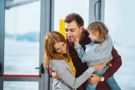happy family smiling while hugging in airport