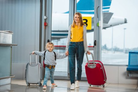 cheerful mother and daughter holding hands in airport