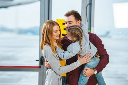 cheerful family smiling while hugging in airport