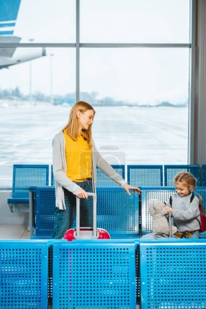 Photo for Attractive mother standing with cute daughter holding teddy bear near baggage in airport - Royalty Free Image