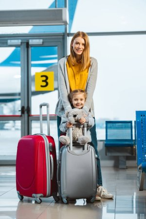 cheerful mother hugging cute daughter holding teddy bear near baggage in airport