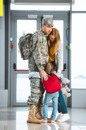 daughter hugging mother and dad in military uniform in airport