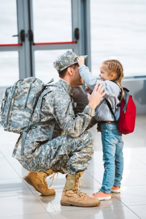 cute daughter touching cap of father in military uniform