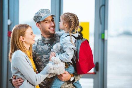 Photo pour Souriant père en uniforme militaire tenant dans les bras fille près de femme à l'aéroport - image libre de droit