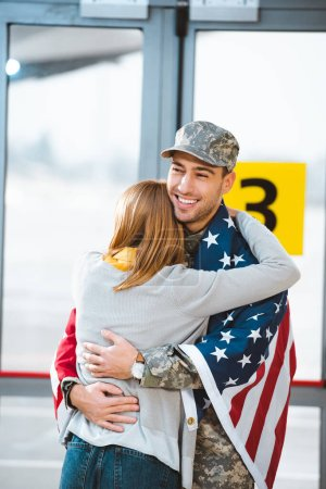 back view of woman hugging boyfriend in military uniform with american flag in airport