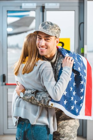 back view of woman hugging smiling boyfriend in military uniform with american flag in airport