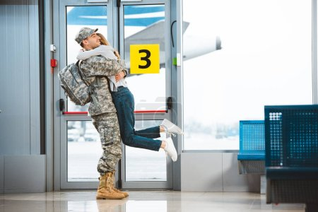 happy boyfriend in military uniform holding in arms girlfriend in airport