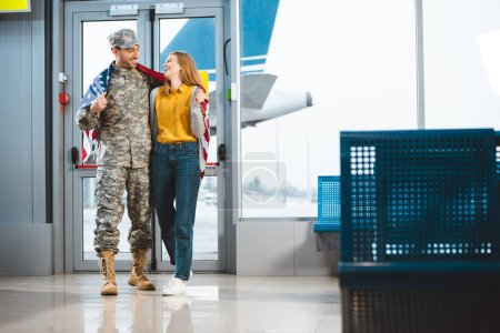 cheerful veteran in military uniform standing with girlfriend and holding american flag in airport