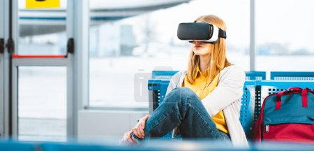 Photo for Woman wearing virtual reality headset while waiting in departure lounge near backpack - Royalty Free Image